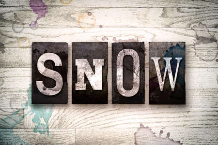 flurry: The word SNOW written in vintage dirty metal letterpress type on a whitewashed wooden background with ink and paint stains. Stock Photo