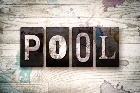 inground: The word POOL written in vintage dirty metal letterpress type on a whitewashed wooden background with ink and paint stains.