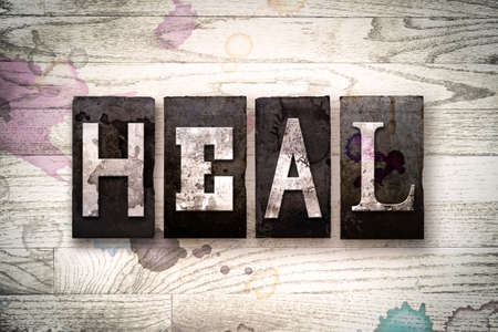 The word HEAL written in vintage dirty metal letterpress type on a whitewashed wooden background with ink and paint stains.