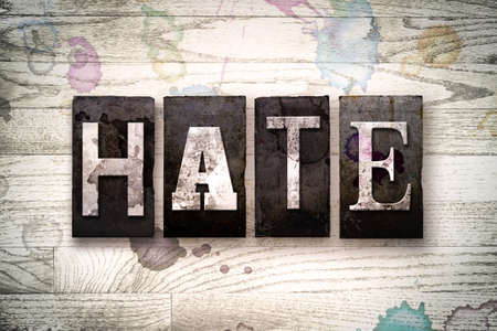 resent: The word HATE written in vintage dirty metal letterpress type on a whitewashed wooden background with ink and paint stains.