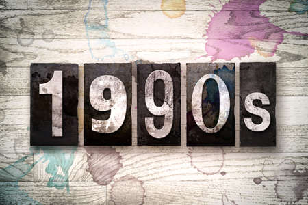 nineties: The word 1990s written in vintage dirty metal letterpress type on a whitewashed wooden background with ink and paint stains.