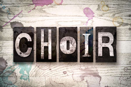 The word CHOIR written in vintage dirty metal letterpress type on a whitewashed wooden background with ink and paint stains.