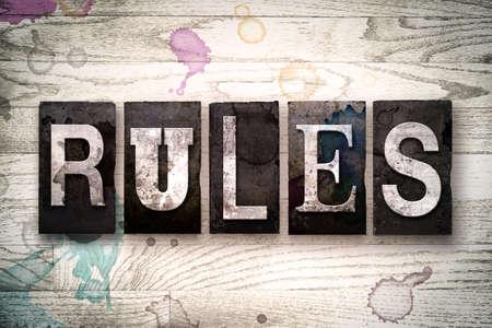 """edicto: La palabra """"reglas"""" escritas en el tipo de tipografía de metal sucio de la vendimia en un fondo de madera blanqueada con manchas de tinta y pintura."""