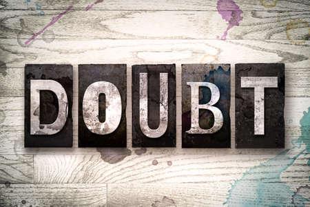 """desconfianza: La palabra """"duda"""" escrito en el tipo de tipograf�a de metal sucio de la vendimia en un fondo de madera blanqueada con manchas de tinta y pintura."""
