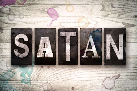 antichrist: The word SATAN written in vintage dirty metal letterpress type on a whitewashed wooden background with ink and paint stains.