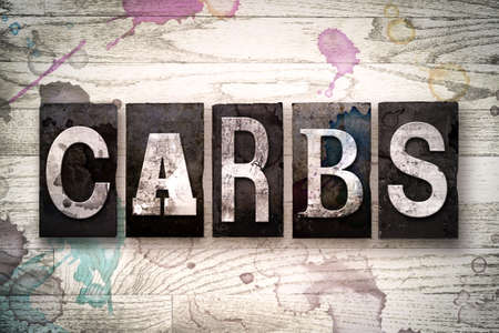carbs: The word CARBS written in vintage dirty metal letterpress type on a whitewashed wooden background with ink and paint stains.
