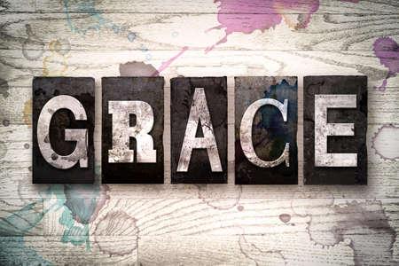 """La parola """"grazia"""" scritto in tipo vintage metal tipografica sporca su uno sfondo di legno intonacato di bianco con macchie di inchiostro e vernice."""