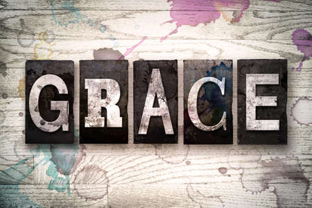 "The word ""GRACE"" written in vintage dirty metal letterpress type on a whitewashed wooden background with ink and paint stains."