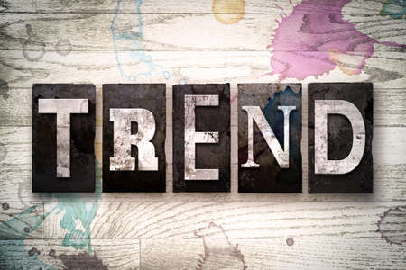 The word TREND written in vintage dirty metal letterpress type on a whitewashed wooden background with ink and paint stains. Stock Photo