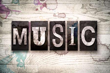 """letras musicales: La palabra """"MUSIC"""", escrita en el tipo de tipografía de metal sucio de la vendimia en un fondo de madera blanqueada con manchas de tinta y pintura."""