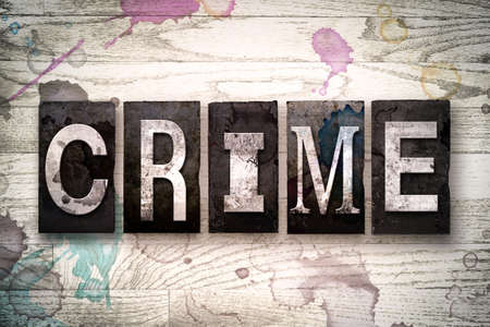 armed robbery: The word CRIME written in vintage dirty metal letterpress type on a whitewashed wooden background with ink and paint stains. Stock Photo