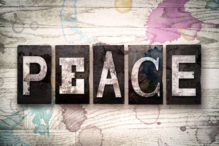 ceasefire: The word PEACE written in vintage dirty metal letterpress type on a whitewashed wooden background with ink and paint stains. Stock Photo