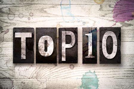"""La palabra """"TOP 10"""" escrita en el tipo de tipografía de metal sucio de la vendimia en un fondo de madera blanqueada con manchas de tinta y pintura. Foto de archivo - 61709747"""