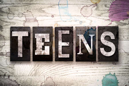 youthfulness: The word TEENS written in vintage dirty metal letterpress type on a whitewashed wooden background with ink and paint stains.