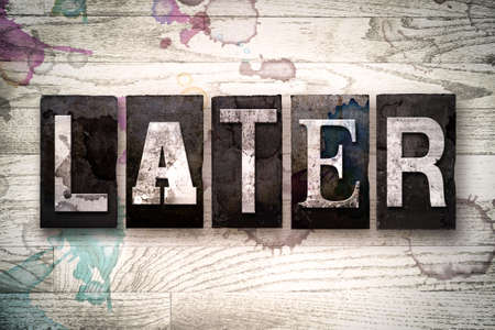 lateness: The word LATER written in vintage dirty metal letterpress type on a whitewashed wooden background with ink and paint stains. Stock Photo