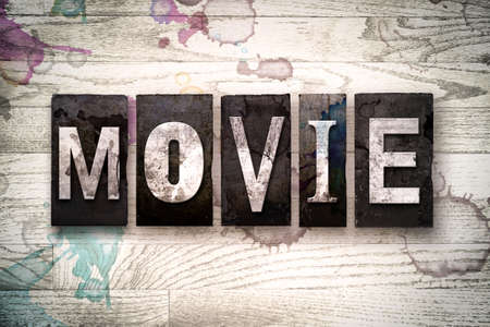 The word MOVIE written in vintage dirty metal letterpress type on a whitewashed wooden background with ink and paint stains.