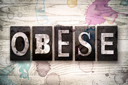 childhood obesity: The word OBESE written in vintage dirty metal letterpress type on a whitewashed wooden background with ink and paint stains.