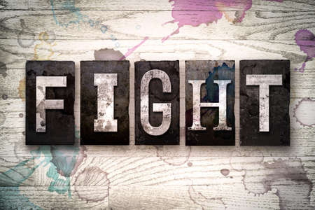 brawl: The word FIGHT written in vintage dirty metal letterpress type on a whitewashed wooden background with ink and paint stains.