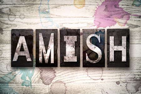 amish: The word AMISH written in vintage dirty metal letterpress type on a whitewashed wooden background with ink and paint stains.