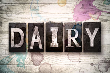 intolerant: The word DAIRY written in vintage dirty metal letterpress type on a whitewashed wooden background with ink and paint stains. Stock Photo