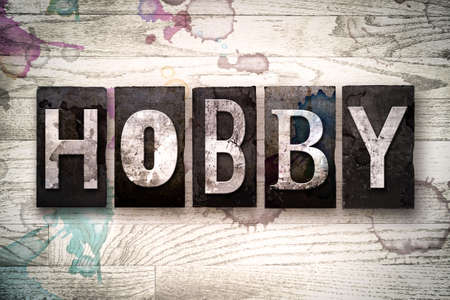 craze: The word HOBBY written in vintage dirty metal letterpress type on a whitewashed wooden background with ink and paint stains.