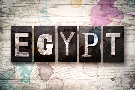 whitewashed: The word EGYPT written in vintage dirty metal letterpress type on a whitewashed wooden background with ink and paint stains.