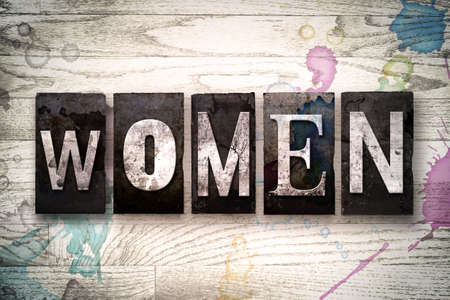 matron: The word WOMEN written in vintage dirty metal letterpress type on a whitewashed wooden background with ink and paint stains. Stock Photo
