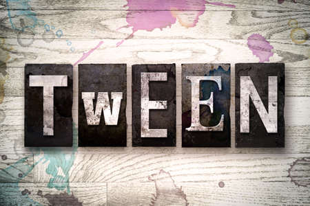 tween: The word TWEEN written in vintage dirty metal letterpress type on a whitewashed wooden background with ink and paint stains.