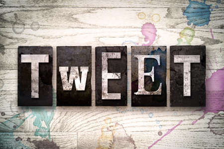 tweets: The word TWEET written in vintage dirty metal letterpress type on a whitewashed wooden background with ink and paint stains.