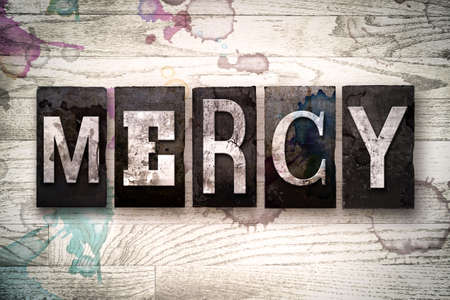 clemency: The word MERCY written in vintage dirty metal letterpress type on a whitewashed wooden background with ink and paint stains.
