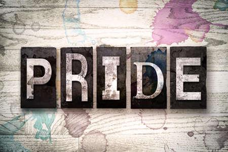 """Le mot """"PRIDE"""" écrit en cru sale letterpress type de métal sur un fond en bois blanchie à la chaux avec de l'encre et de peinture aux taches."""