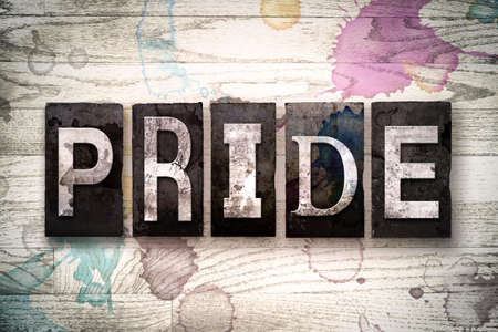 self worth: The word PRIDE written in vintage dirty metal letterpress type on a whitewashed wooden background with ink and paint stains.