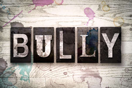 harass: The word BULLY written in vintage dirty metal letterpress type on a whitewashed wooden background with ink and paint stains.