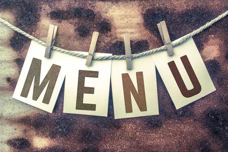 """Het woord """"MENU"""" werd op kaarten gestempeld en aan een oud stuk touw op een geroeste metalen achtergrond geprikt."""