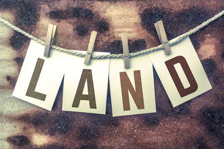 The word LAND stamped on cards and pinned to an old piece of twine over a rusted metal background.