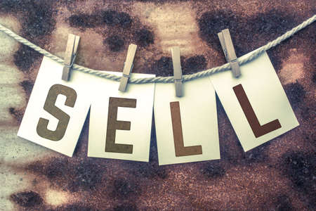 sale sign: The word SELL stamped on cards and pinned to an old piece of twine over a rusted metal background.
