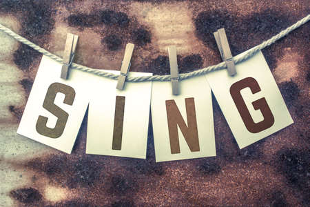 serenade: The word SING stamped on cards and pinned to an old piece of twine over a rusted metal background. Stock Photo