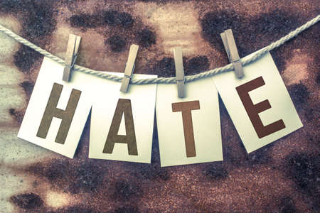 resent: The word HATE stamped on cards and pinned to an old piece of twine over a rusted metal background. Stock Photo