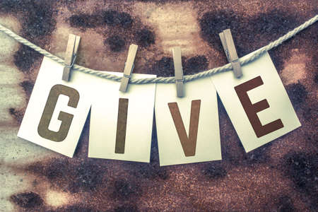 endow: The word GIVE stamped on cards and pinned to an old piece of twine over a rusted metal background. Stock Photo