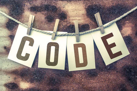 secret code: The word CODE stamped on cards and pinned to an old piece of twine over a rusted metal background.