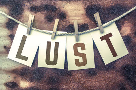 The word LUST stamped on cards and pinned to an old piece of twine over a rusted metal background. Stock Photo