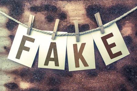 scamming: The word FAKE stamped on cards and pinned to an old piece of twine over a rusted metal background. Stock Photo