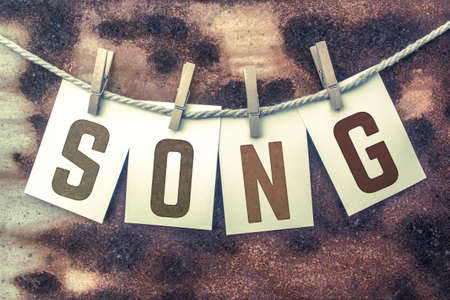 chorale: The word SONG stamped on cards and pinned to an old piece of twine over a rusted metal background. Stock Photo