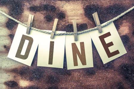 """Het woord """"DINE"""" gestempeld op kaarten en vastgemaakt aan een oud stuk touw over een verroeste metalen achtergrond. Stockfoto"""
