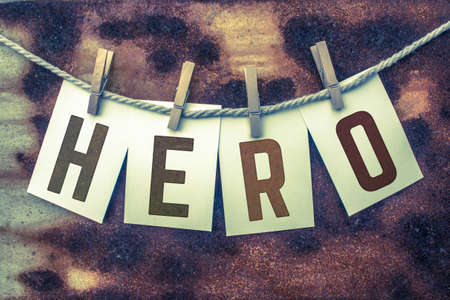 clothes pins: The word HERO stamped on card stock hanging from old twine and clothes pins over a rusty vintage background.