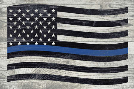 white washed: A police law enforcement flag with blue stripe over a white washed wooden floor.