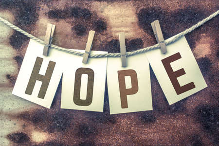 The word HOPE stamped on cards and pinned to an old piece of twine over a rusted metal background. Stock Photo