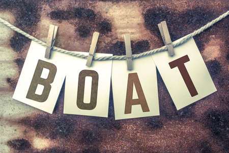 boater: The word BOAT stamped on cards and pinned to an old piece of twine over a rusted metal background.