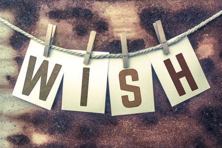 yearning: The word WISH stamped on cards and pinned to an old piece of twine over a rusted metal background. Stock Photo