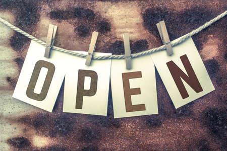"""Het woord """"OPEN"""" wordt op kaarten gestempeld en aan een oud stuk touw gespeld over een geroeste metalen achtergrond."""
